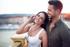 年轻都市由耳机的夫妇听的音乐在户外 免版税库存照片