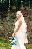 年轻金发新娘在草站立在一个异乎寻常的公园在石墙附近 库存照片