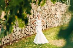 年轻金发新娘在草站立在一个异乎寻常的公园在石墙附近 图库摄影