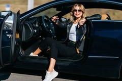 年轻金发碧眼的女人照片有坐在有门户开放主义的汽车的钥匙的 库存照片