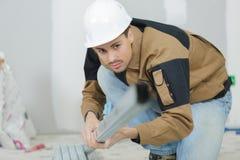 年轻金属工在建造场所控制金属棒 库存照片