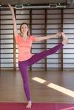 年轻镇静俏丽的解决妇女佩带的白色的运动服,做瑜伽或pilates锻炼 全长 免版税库存照片