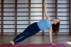 年轻镇静俏丽的解决妇女佩带的白色的运动服,做瑜伽或pilates锻炼 全长 免版税图库摄影