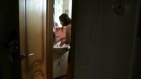 年轻长发妇女洗涤物面孔,手和刷他的牙在卫生间里 蓝色女睡袍的女孩打开 影视素材
