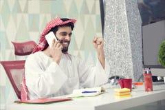 年轻阿拉伯商人谈话在手机和运作的财务关于费用与便携式计算机 图库摄影