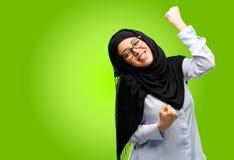 年轻阿拉伯妇女佩带的hijab被隔绝在绿色背景 库存图片