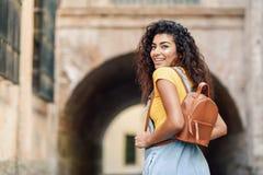 年轻阿拉伯妇女背面图有户外背包的 便服的旅客女孩在街道 愉快的女性佩带的黄色t 免版税库存照片