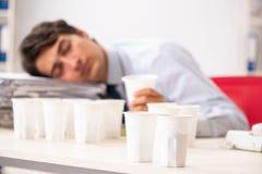年轻雇员使上瘾对咖啡 图库摄影