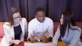 年轻雇员谈论经营计划在非正式会议上在餐馆 股票录像