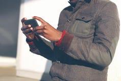 年轻非洲人在城市使用一个智能手机 免版税库存照片