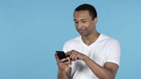 年轻非洲人浏览智能手机,蓝色背景 股票录像
