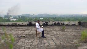年轻非洲医生坐被破坏的医院的屋顶并且读书在背景  股票视频
