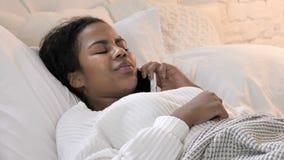 年轻非洲妇女谈话在电话,当放置在床上时 影视素材