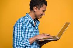 年轻非裔美国人的人与膝上型计算机一起使用 图库摄影