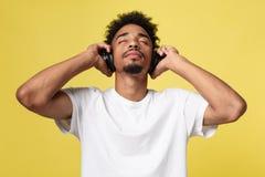 年轻非裔美国人的人佩带的耳机和享受在金银铜合金背景的音乐 图库摄影
