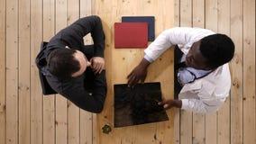年轻非裔美国人的医生与患者协商 免版税库存照片