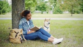 年轻非裔美国人的夫人是坐草坪在公园和抚摸她的充满爱的阅读书纯血统爱犬和 股票录像