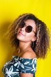 年轻非裔美国人的女孩秀丽画象有非洲的发型的 摆在黄色背景的女孩,看照相机 嘘演播室 免版税图库摄影