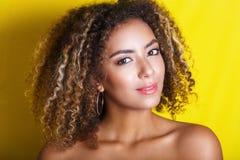 年轻非裔美国人的女孩秀丽画象有非洲的发型的 摆在黄色背景的女孩,看照相机 库存图片