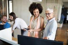 年轻非裔美国人的妇女与片剂一起使用在办公室 免版税库存照片