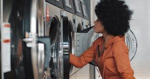年轻非裔美国人的妇女在洗衣机前面坐并且用肮脏的洗衣店装载洗衣机 ?? 股票录像