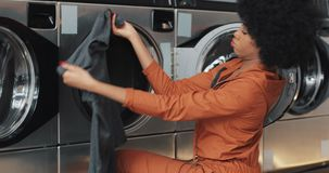 年轻非裔美国人的妇女在洗衣机前面坐并且用肮脏的洗衣店装载洗衣机 ?? 股票视频