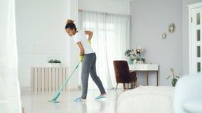 年轻非裔美国人的妇女清洗地板在现代房子里与拖把,俏丽的女孩佩带的家庭衣物,拖鞋和 股票录像