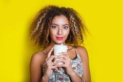 年轻非裔美国人的妇女秀丽画象有非洲的发型的 摆在用在黄色背景的咖啡的女孩,看来了 免版税库存图片