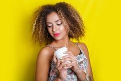 年轻非裔美国人的妇女秀丽画象有非洲的发型的 摆在用在黄色背景的咖啡的女孩,看来了 库存图片