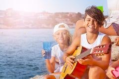 年轻音乐家弹吉他在与朋友的远足 图库摄影