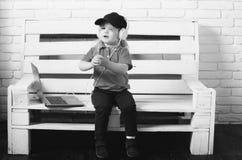 年轻音乐迷 耳机的小男孩听音乐, audiobook,研究膝上型计算机 免版税库存图片