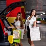 年轻顾客在汽车投入了购买 库存图片
