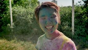 年轻颜色的cheerfyl亚裔女孩投掷与在holi节日的五颜六色的粉末自白天在夏天,颜色概念 股票录像