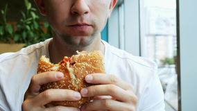 年轻饥饿的人特写镜头吃在咖啡馆的汉堡包,便当餐馆 股票视频