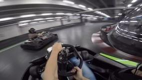 年轻驾驶休闲在karting的膝部种族极端体育行动的人华美的第一个人pov去推车汽车在竞技场里面 股票录像