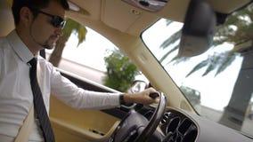 年轻驾驶凉快的汽车,在城市的美丽的景色的商人佩带的太阳镜 股票视频