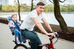 年轻骑一辆自行车的父亲和女儿在公园 免版税库存图片