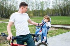 年轻骑一辆自行车的父亲和女儿在公园 库存照片