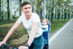 年轻骑一辆自行车的父亲和女儿在公园 图库摄影