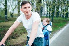 年轻骑一辆自行车的父亲和女儿在公园 免版税图库摄影