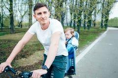 年轻骑一辆自行车的父亲和女儿在公园 库存图片