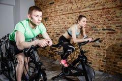 年轻骑自行车在健身房的人和妇女,行使做心脏锻炼循环的自行车的腿 免版税库存图片