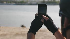 年轻骑自行车者藏品电话在他的为河和城市佩带的盔甲、太阳镜和手套照相的手上 t 影视素材