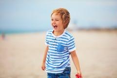 年轻高兴男孩,使用与玩具推进器的孩子,获得在夏天海滩的乐趣 免版税库存图片