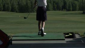 年轻高尔夫球运动员实践他的在开车范围,看的高尔夫球摇摆从旁边 影视素材