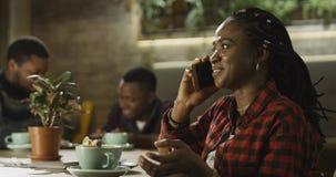 年轻黑人妇女谈话在她的手机 免版税库存图片