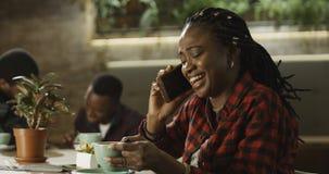 年轻黑人妇女谈话在她的手机 免版税图库摄影