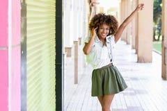 年轻黑人妇女,非洲的发型,在有headphon的都市街道 库存图片