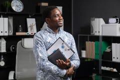 年轻黑商人画象与财政文件的在他的站立在桌附近的手上在办公室 库存照片