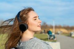 年轻,愉快的红头发人女孩在春天在河附近的公园听到音乐通过无线bluetooth耳机 免版税库存图片